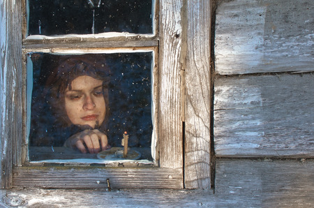 peasant woman is resting by the window near a burning Church candle in the winter evening, maybe she is waiting for someone Stock Photo