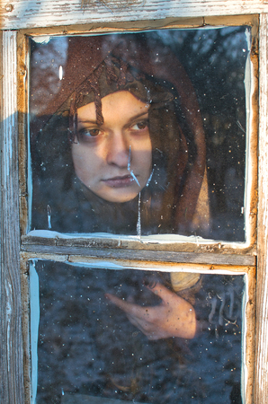 a sad woman with bruises under her eyes, wrapped in wool, looks sadly at the shabby window of an old hut, maybe she does not have to live and from this depression befell her? Stock Photo