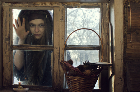 monstrous witch scratches and scrapes at the window of the village hut on a winter day in the hope of intimidating the inhabitants Stok Fotoğraf