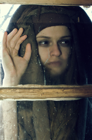an unkind young woman looks into the window of a village house Stock Photo