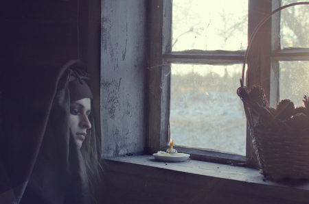 sad medieval woman sitting in the upper room by the window on a cold winter day and waiting for who knows what... maybe the man is waiting, and maybe someone buried recently Banque d'images