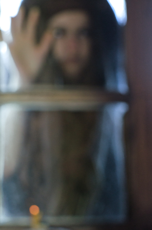 blurry image of a woman looking in the window