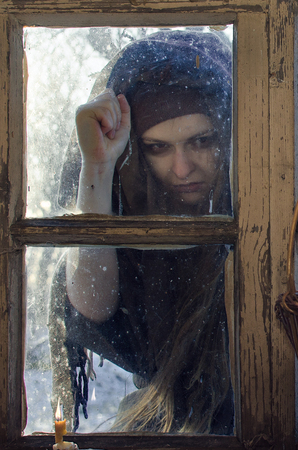extremely unkind rural peasant woman knocks on the window in the winter evening, she brings bad news