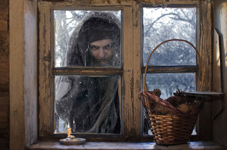 evil witch came to the hut Christmas evening with clearly evil intentions and now looks out the window with a fierce look, it is a very evil and thieving woman, be afraid of her!