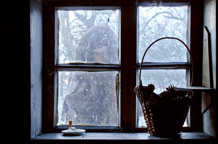 vague silhouette lost in the snow outside the window of a cozy house