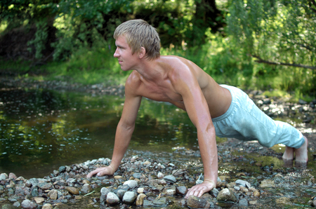 guy doing push-UPS on the rocky shore of the lake