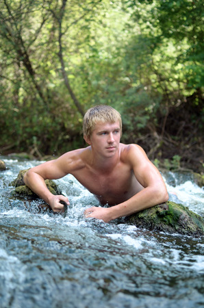 young man resting and bathing in the wild