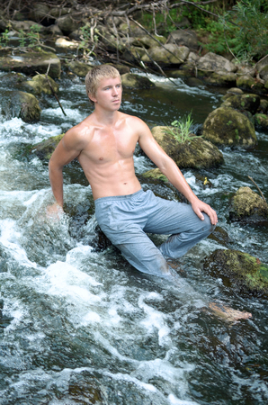 young man resting in nature, swimming in the Northern river