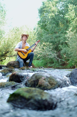 waterfall in the woods and a young man playing guitar Banque d'images