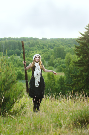 witch with a broom and a black dress to have fun in the woods on a grassy hill Standard-Bild