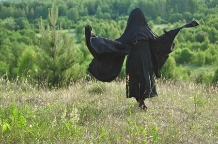 woman witch in a black cloak looks into the woods from a mountain covered with grass