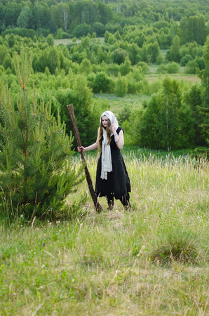 witch with a broom and a black dress stands in the woods on a grassy hill Standard-Bild - 118003918
