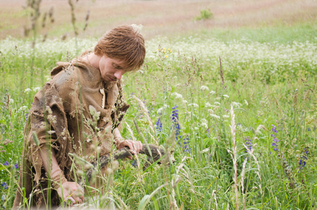 young man dressed as a medieval peasant from burlap in a field