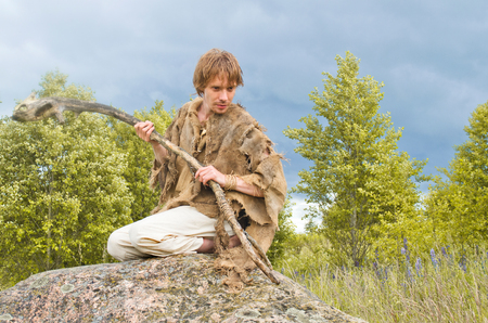 young shaman with a stick from an old stick sits on a huge stone among the herbs and looks at something with interest