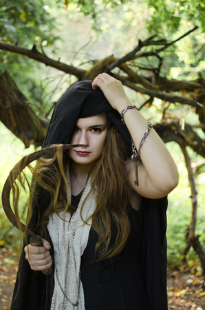 young woman, perhaps a witch in black clothes and a white shawl with a sharp sickle in her hands cut off her hair in order to induce damage and conjure Standard-Bild - 118004052