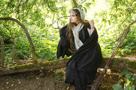 young woman, perhaps a witch in black clothes and a white shawl sits and rests on a tree branch in the garden on a Sunny day Standard-Bild - 118004063