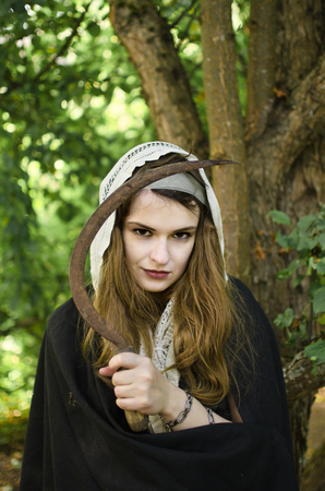 young witch with a sharp rusty sickle smiles at something Standard-Bild - 118004091