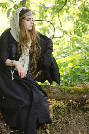 young woman, perhaps a witch in black clothes and a white shawl sits and rests on a tree branch in the garden on a Sunny day Standard-Bild - 118004108