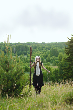 witch with a broom and a black dress to have fun in the woods on a grassy hill Standard-Bild - 118004223