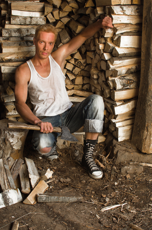 guy with the ax in his hand and a lot of split firewood
