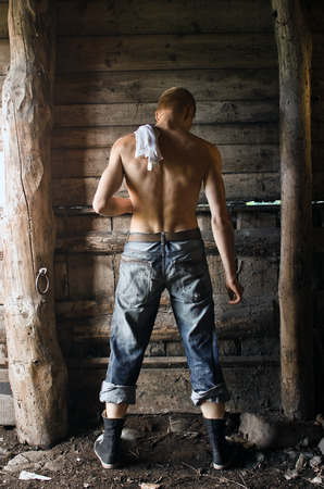 back of a handsome man in a rustic barn
