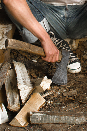 axe in mens hands and chopped wood