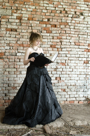 evil Queen in a black ball gown reads the book of witchcraft conceived evil Standard-Bild - 118004954