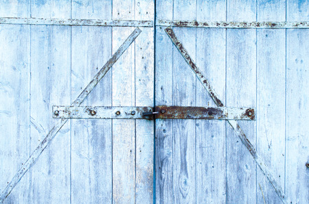 old Board gate of the barn shackled with iron and covered with peeling paint-background image Stock Photo