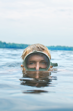 man in a mask for scuba diving emerges from the lake, head close-up