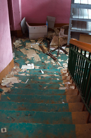 old stairs covered with various debris in an abandoned house