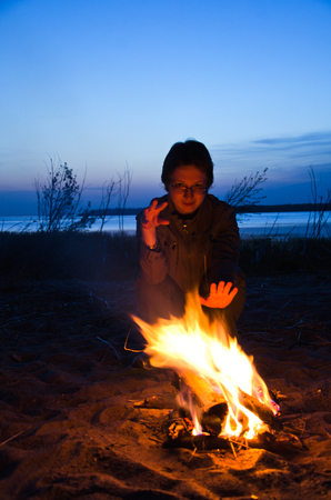 young woman tourist warms hands at night campfire on the beach
