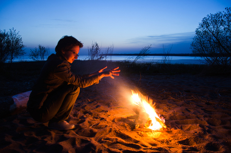 young woman tourist warms hands at night campfire on the beach Standard-Bild - 118005824