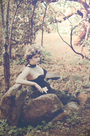 young woman in a lush black dress sits in an old garden amidst a pile of large stones Reklamní fotografie