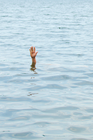 hand of a drowning man leaning out of the water