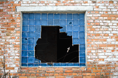 broken window with the remains of blue glass blocks in the old brick wall Reklamní fotografie