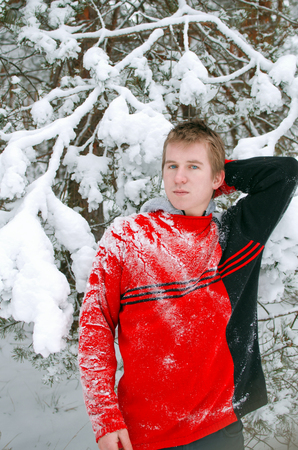 guy in the winter forest in a sweater sprinkled with snow