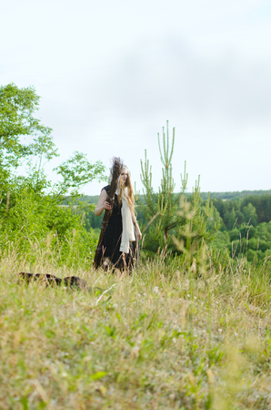 young witch is wandering in a meadow among young trees looking for something