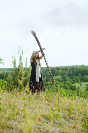 young witch turns a broom standing in the field, probably conjures 写真素材