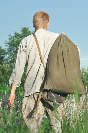 soldier with a large duffel is among the herbs