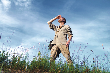 guy in the old military uniform of the second world war in full growth in the field against the cloudy blue sky Stock Photo