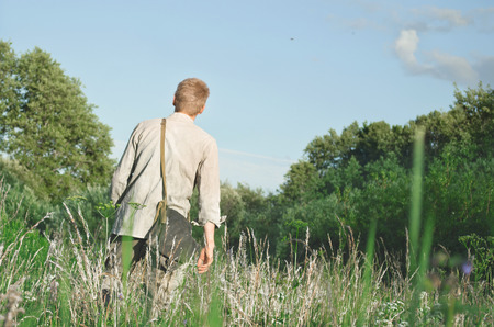 soldier is on the field touching the hand of tall grass