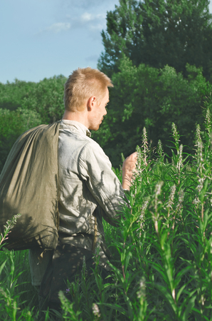 man in an old military uniform standing in the field considering the tall herbaceous plants