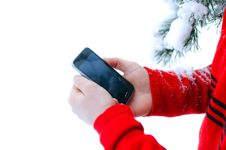 mobile phone with touch control in men's hands and pine branch covered with snow on white background