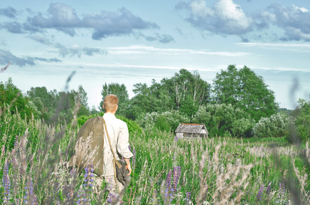 man in an old world war II uniform in a field among tall wild grasses with a big bag in his hands