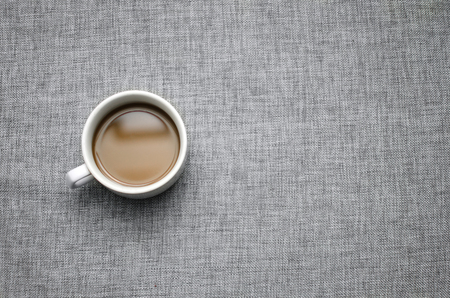 Cup of coffee on grey fabric surface close-up-background image 写真素材