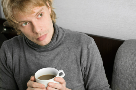 young man in a gray sweater with a Cup of coffee in his hands