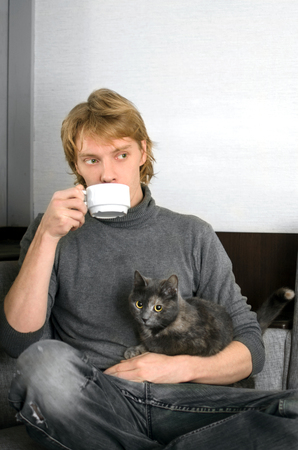 young man in a gray sweater with a Cup of coffee in his hands and his gray cat Stock Photo
