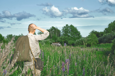 soldier in an old world war II uniform in a field among tall wild grasses with a large bag in his hands laying his hand behind his head looking forward