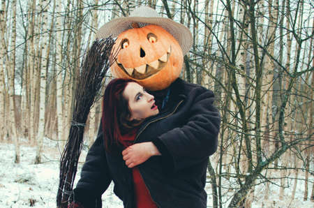 Halloween Scarecrow with a pumpkin on his head and an evil witch with a broom in her hands met in the woods 写真素材