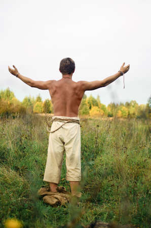 young man stripped to the waist stands in a wild field with his arms outstretched 写真素材